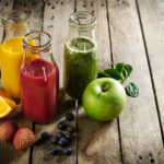 Tasty colorful fresh homemade smoothies in glass jars on wooden
